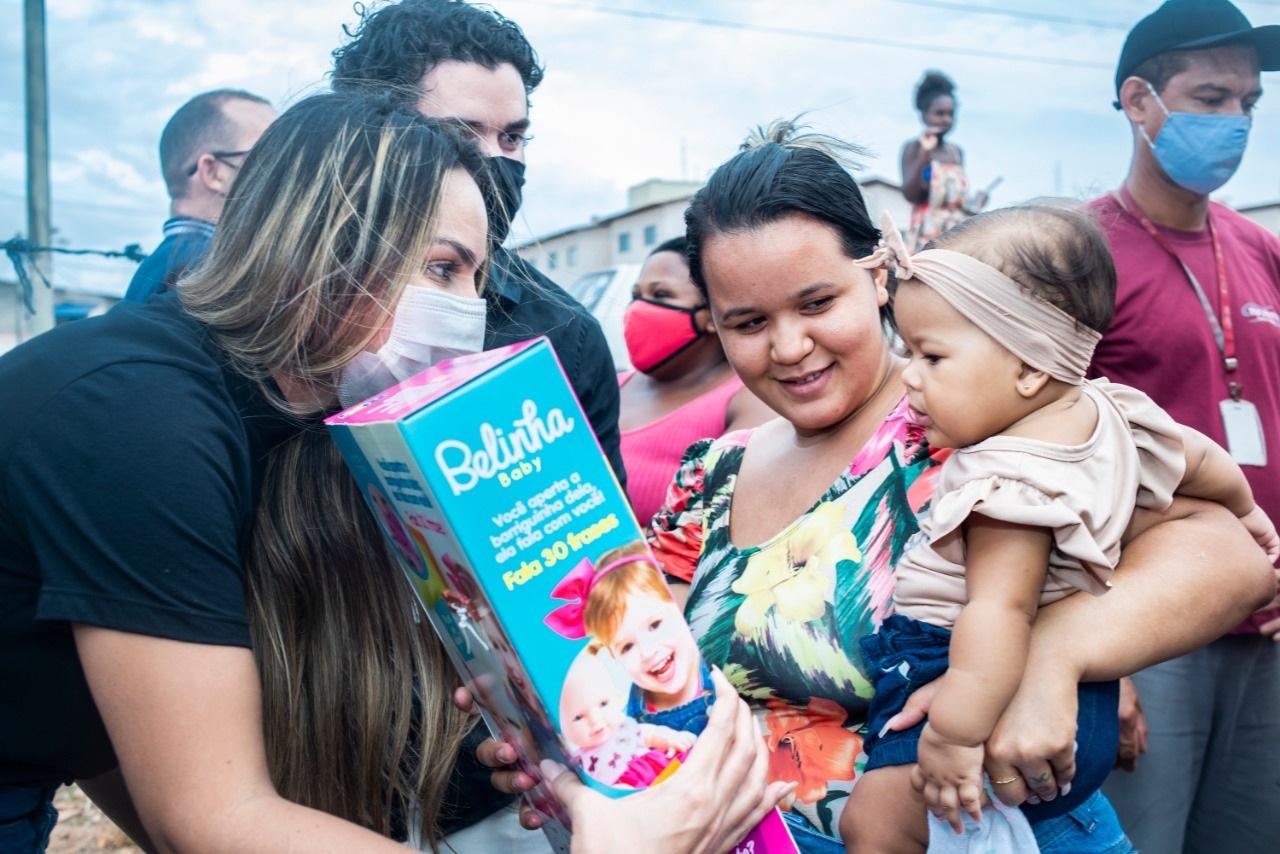 A presidente do Gedema entrega brinquedo à pequena moradora da Ilhinha