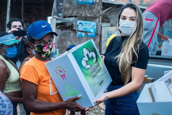 Dona de casa recebe cesta básica das mãos de Ana Paula Lobato durante ação do Gedema Solidário