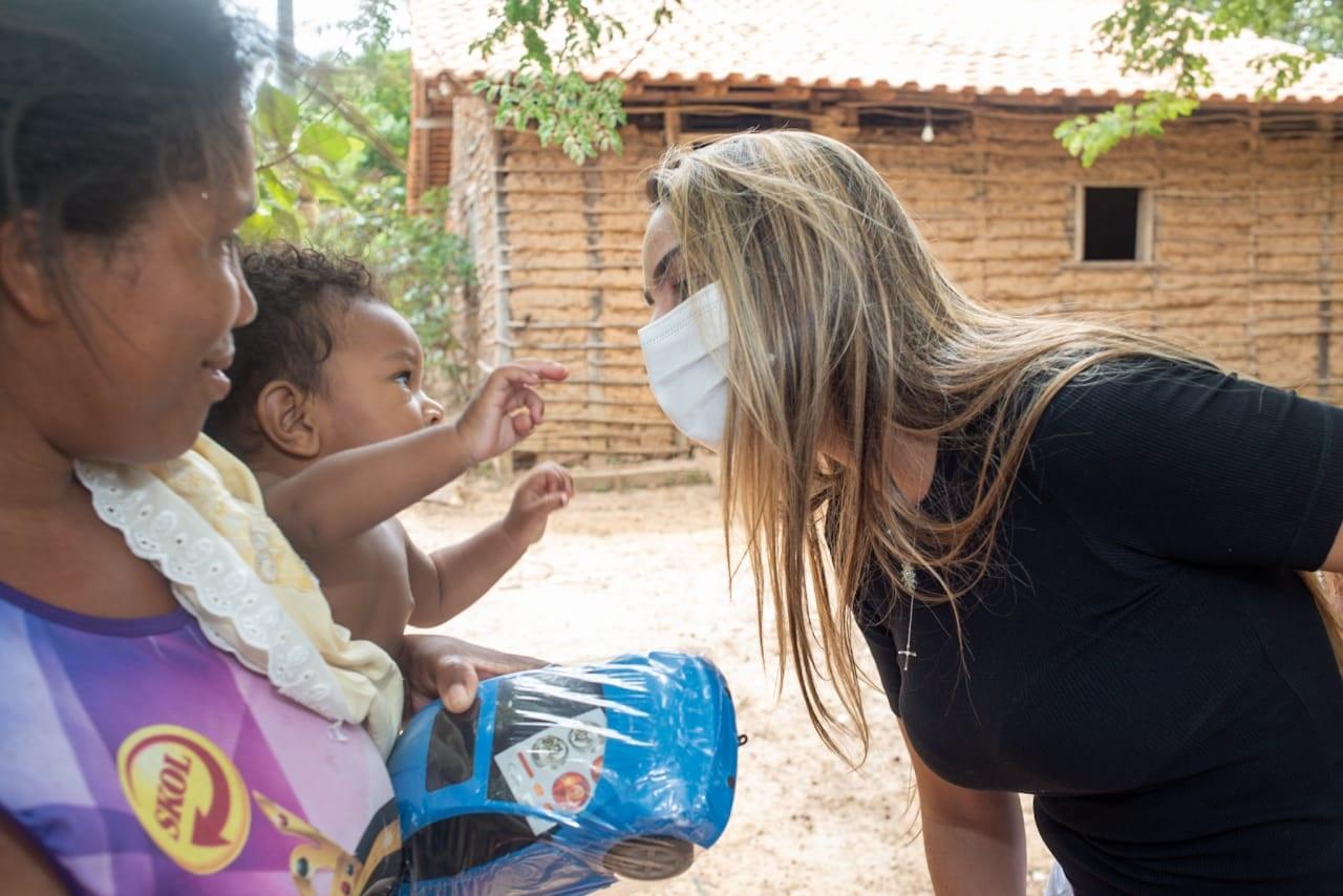 Ana Paula brinca com bebê durante entrega de brinquedos em povoado de Pinheiro