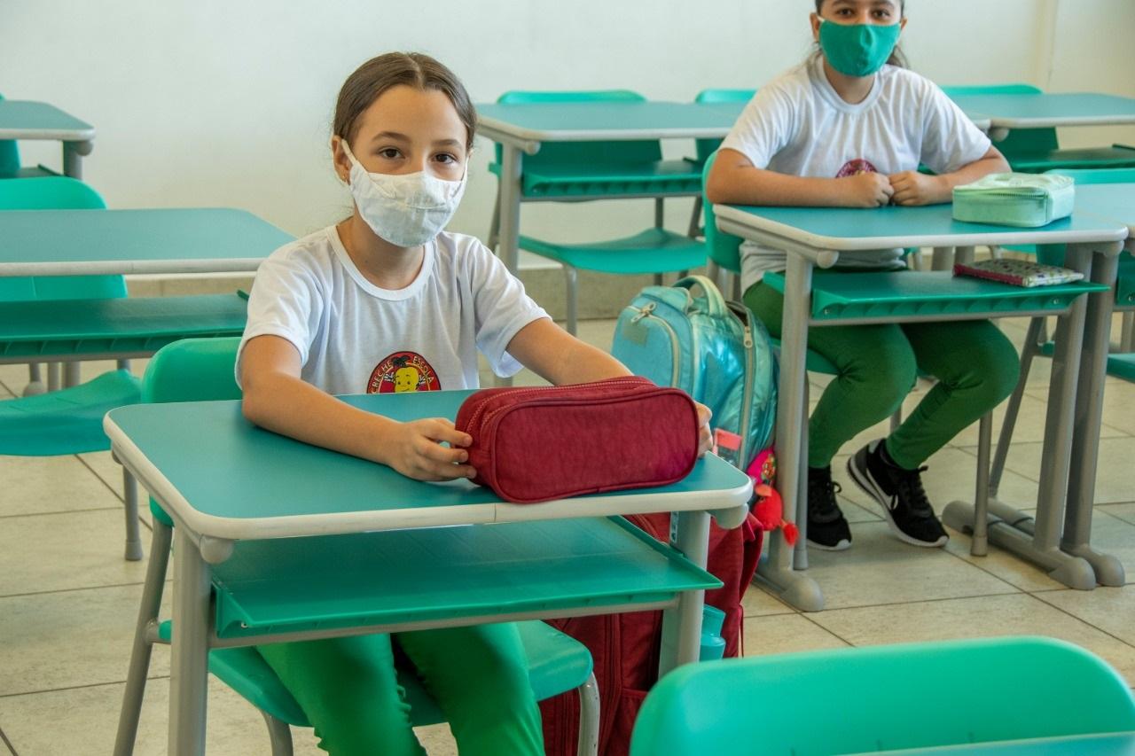 Alunos sentam em carteiras com distanciamento social, seguindo os protocolos sanitários contra a Covi-19
