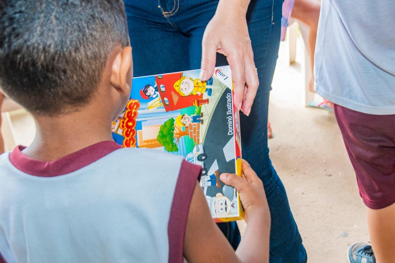 Criança atendida pela instituição recebe seu presente no ato de doação de brinquedos feito pelo Gedema