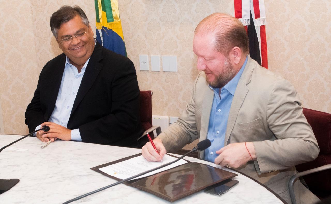 Othelino Neto, observado pelo governador Flávio Dino, assina documento que garantirá a liberação das emendas